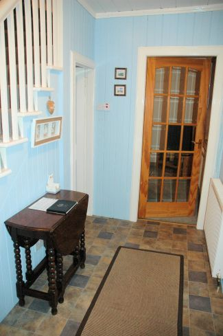 The front door of Bruaich Cottage in Lochcarron opens into the hallway from which there are doors to the kitchen/dining room, the living room and the bathroom. The hall, stairs and landing are pine-clad and tastefully decorated.