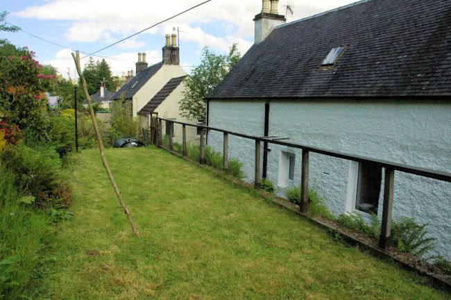 The rear garden at Bruaich Cottage, Lochcarron, slopes upwards steeply but there is a level, grassy area at the foot of the slope.